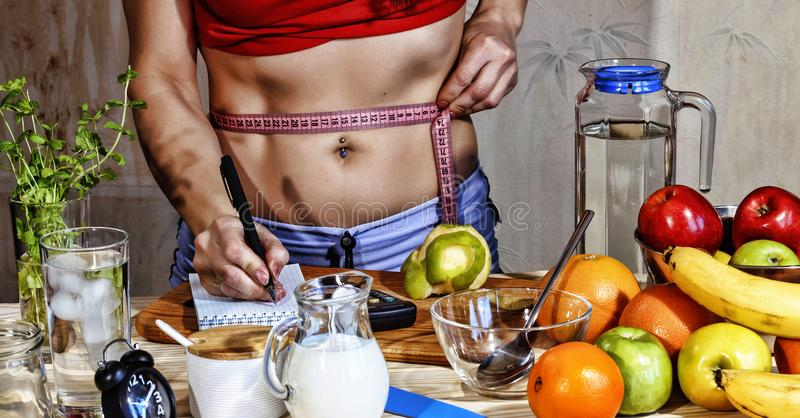 Young woman measures. Detox. Young girl measures the waist and uses proper nutrition. Detox drinks, ingredients, dumbbells. Concep. Young woman measures. Detox stock images
