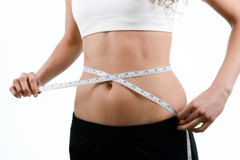 Young woman measuring waist with tape on white background. Young woman dieting and contemplating weight loss measuring waist with tape on white background stock images