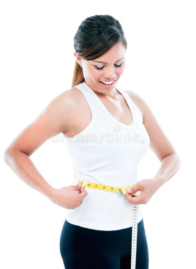 Young Woman Measuring Waistline. Young woman measuring her waistline with a measuring tape over white background stock photography
