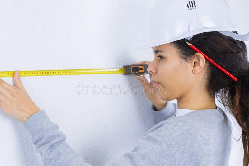 Young woman measuring wall with measuring tape stock image