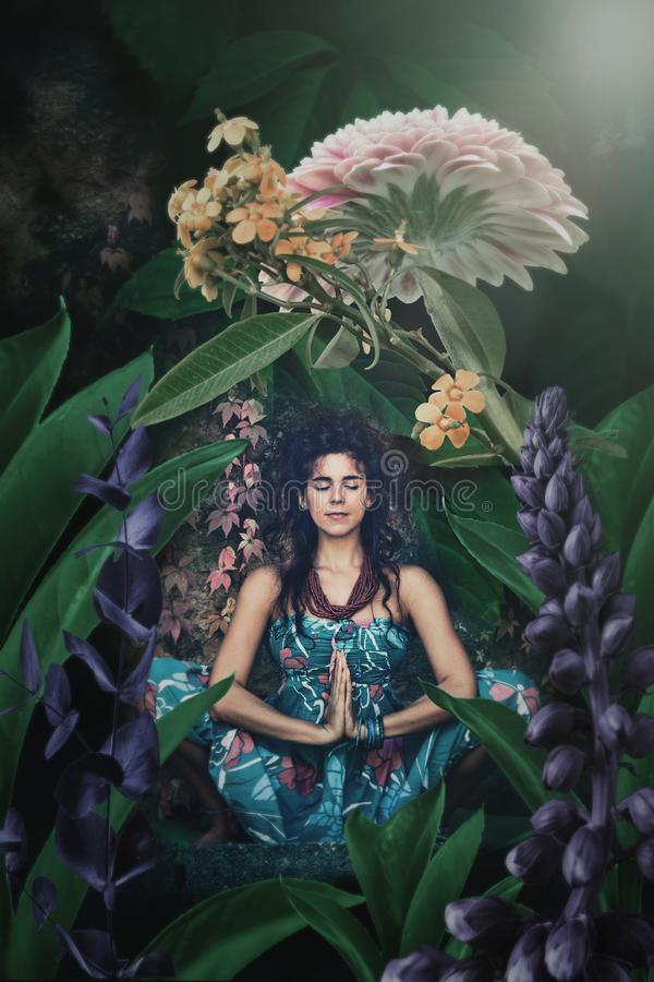 Young woman meditate in yoga position in fantasy garden royalty free stock images