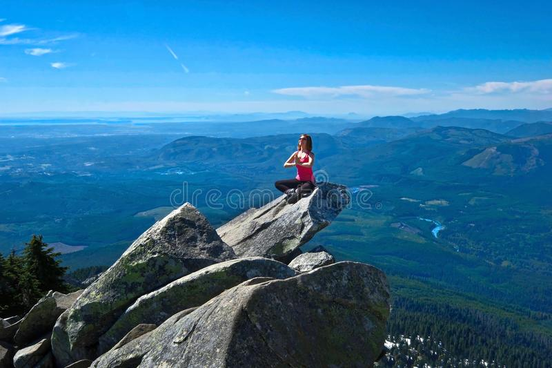 Young woman meditate on rock above beautiful valley. royalty free stock photos