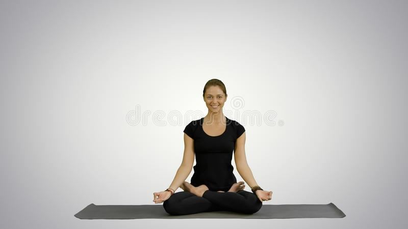 Young woman meditates while practicing yoga on white background royalty free stock image