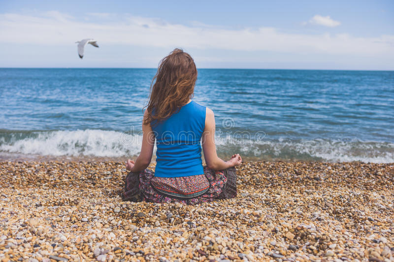 Young woman meditating on the beach. A young woman is sitting on the beach and is meditating royalty free stock photo