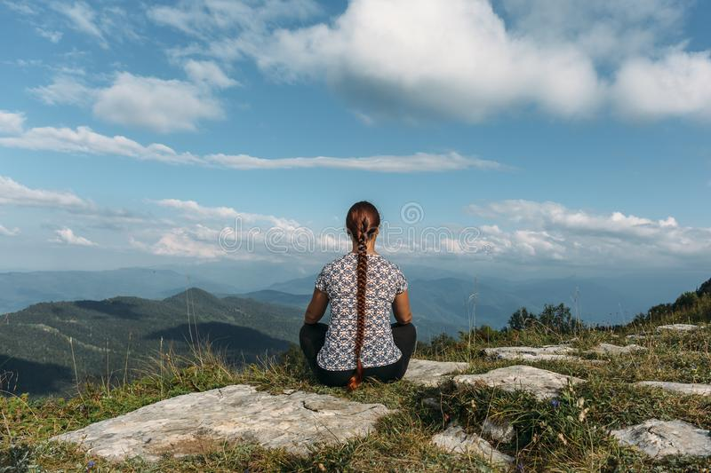 Young woman meditating or doing yoga while sits on rock top with magic mountain landscape royalty free stock photos