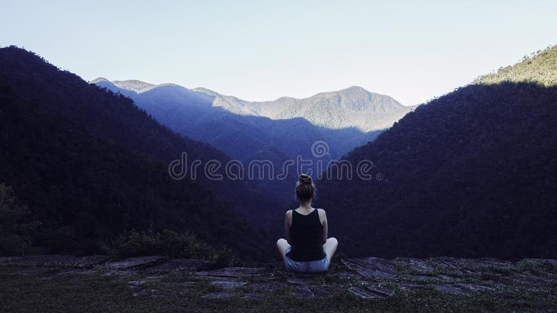 Young woman meditating in the mountains of sierra nevada. Rear view of a young female sitting on the abyss of a platform of Ciudad Perdida, Colombia, overlooking stock images
