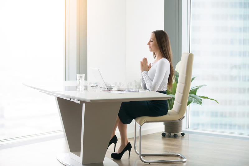 Young woman meditating at the office desk. Young woman meditating at the modern office desk, finding a time in over-packed schedule, yoga as a habit and stock photos