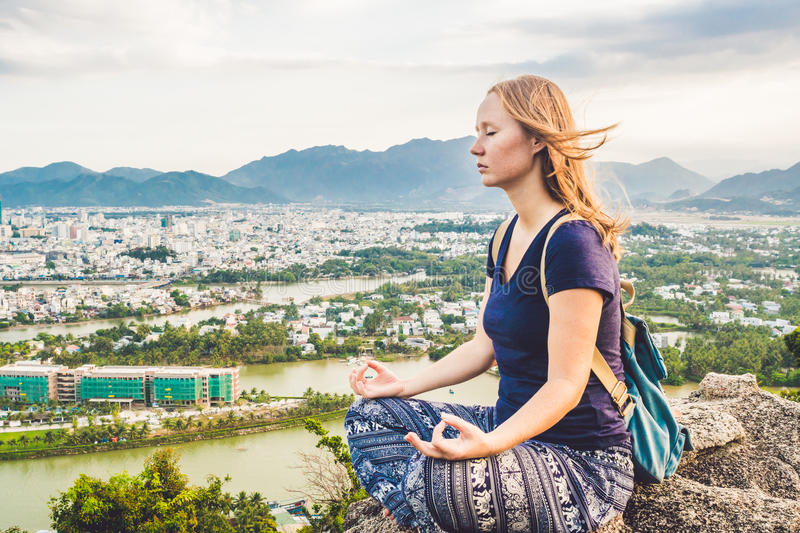 Young woman meditating over ancient city landscape on sunrise Copy space stock images
