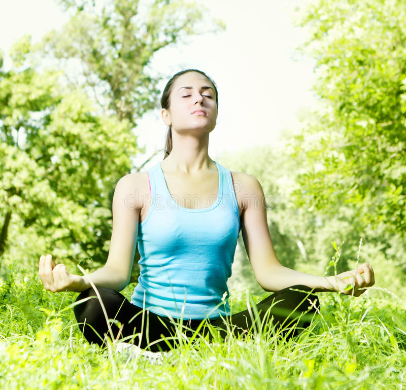 Young woman meditating in the park stock image