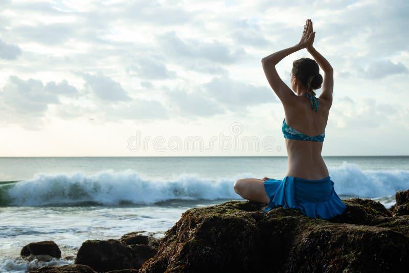 Young woman meditating, practicing yoga and pranayama with namaste mudra at the beach, Bali royalty free stock image