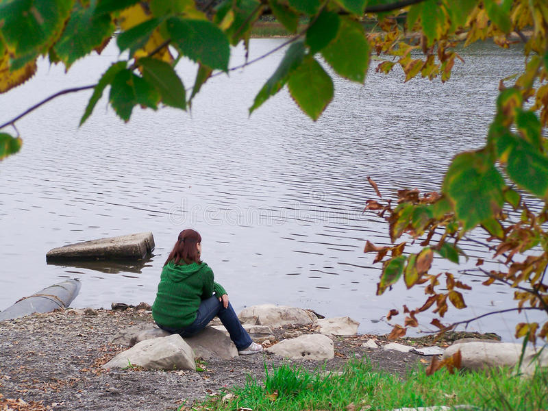 Young woman meditating by the river-Stock Photos royalty free stock images