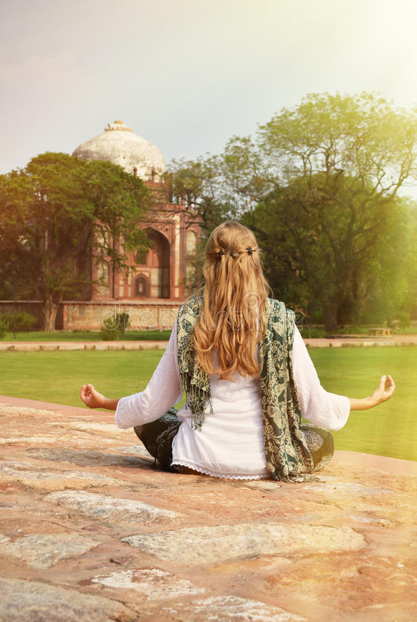 Young woman meditating in the yard of Humayun's Tomb. Delhi, Ind stock image
