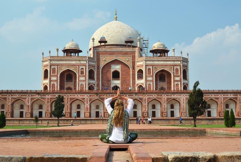 Young woman meditating in the yard of Humayun's Tomb. Delhi royalty free stock photo
