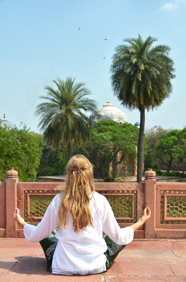 Young woman meditating in the yard of Humayun's Tomb. Delhi stock image