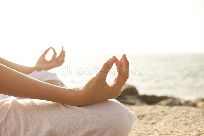 Young woman meditation in a yoga pose on the tropical beach. royalty free stock photography
