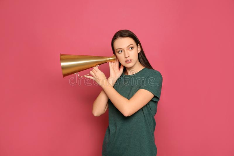Young woman with megaphone. On color background stock image