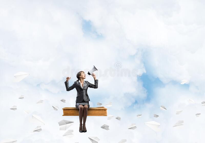 Young woman with megaphone sitting on big book royalty free stock photos