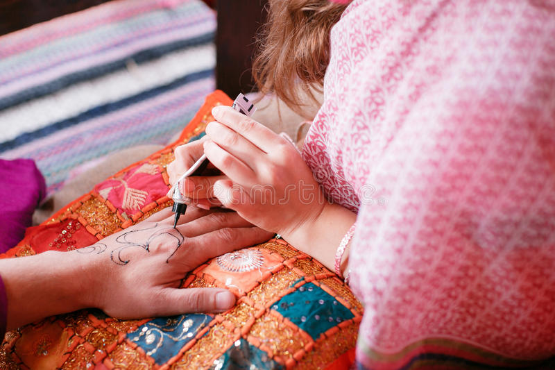 Young woman mehendi artist painting henna on the hand for man stock photos
