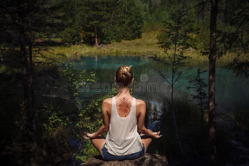 Young woman with mehendi on her back meditating near blue mountain lake royalty free stock image