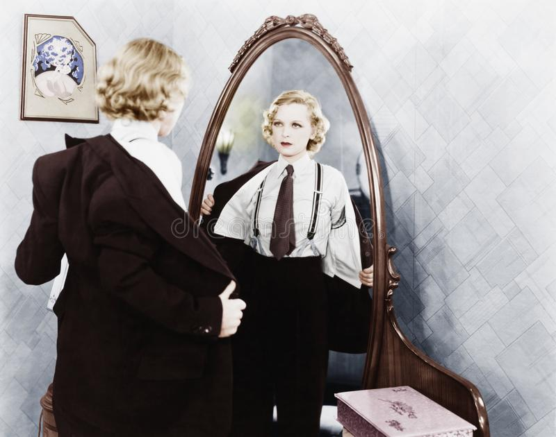 Young woman in men's clothing getting undressed in front of a mirror stock photo