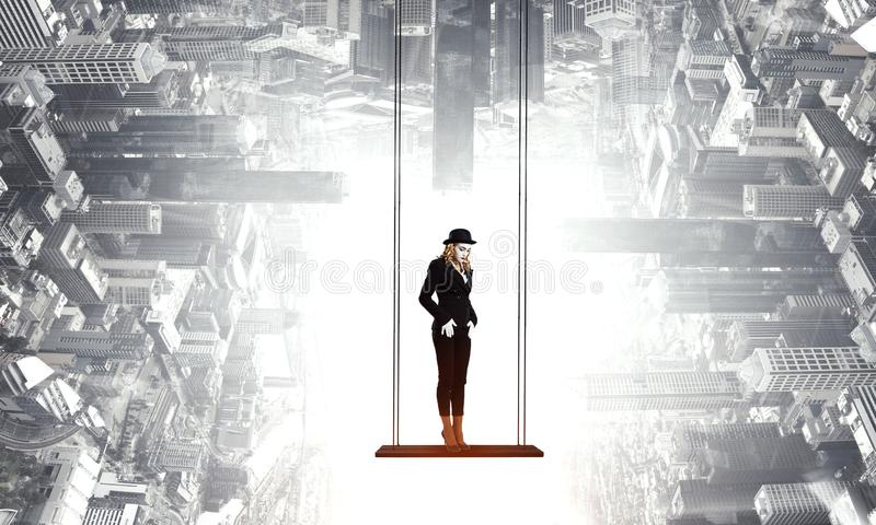 Young woman mime. Mixed media. Mime woman in black suit riding swing. Mixed media royalty free stock images