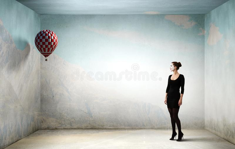 Young woman mime. Mixed media. Woman mime in black suit standing in empty room. Mixed media stock photos