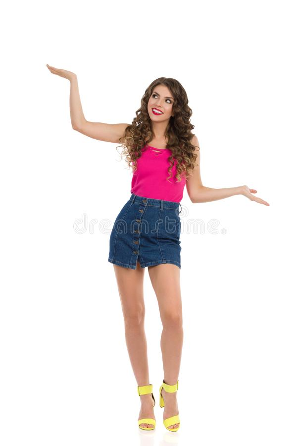Young Woman In Mini Skirt And High Heels Is Holding Hands Raised And Comparing Something. Beautiful young woman in jeans mini skirt, pink top and high heels is royalty free stock photography