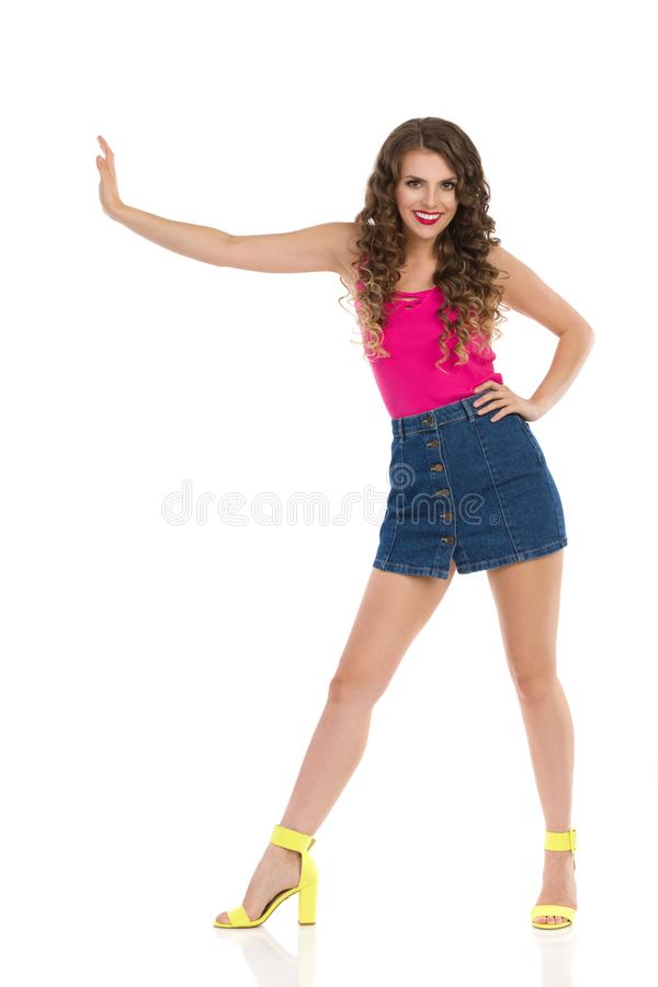 Young Woman In Mini Skirt And High Heels Is Lean Or Pushing Something. Smiling young woman in jeans mini skirt, pink top and high heels is standing legs apart royalty free stock images