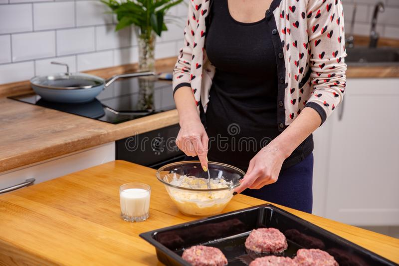 Young woman mixing cheese dough with a spoon in kitchen. Home cooking of meat dish royalty free stock photography