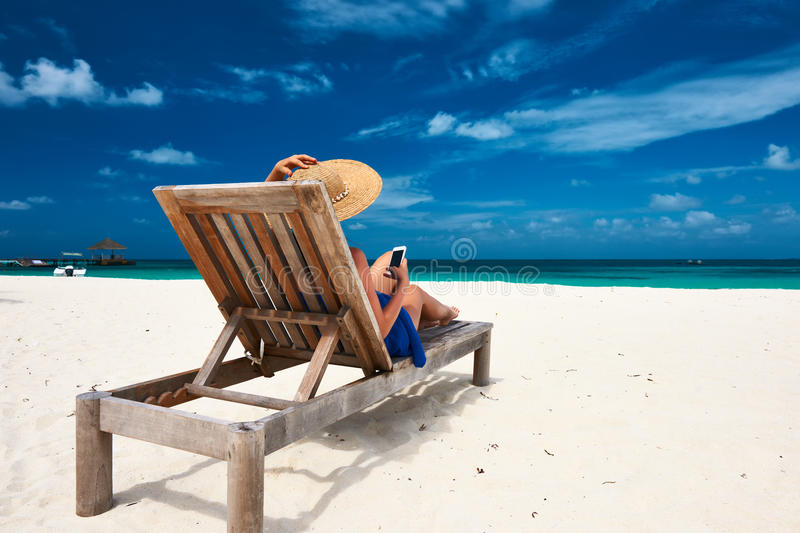 Young woman with mobile phone at the beach stock image