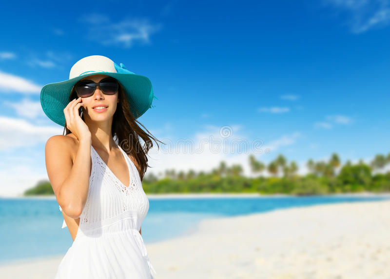 Young woman with mobile phone on a beach stock images