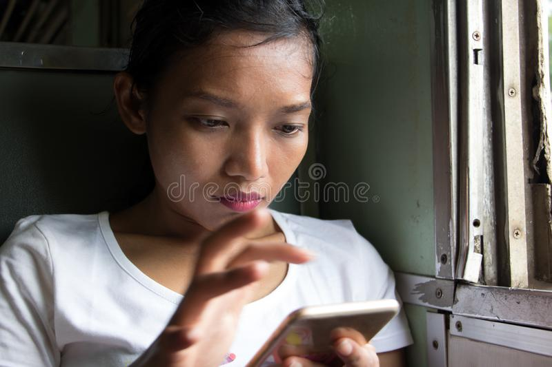 A young woman with mobile phone rides in old train. royalty free stock photos