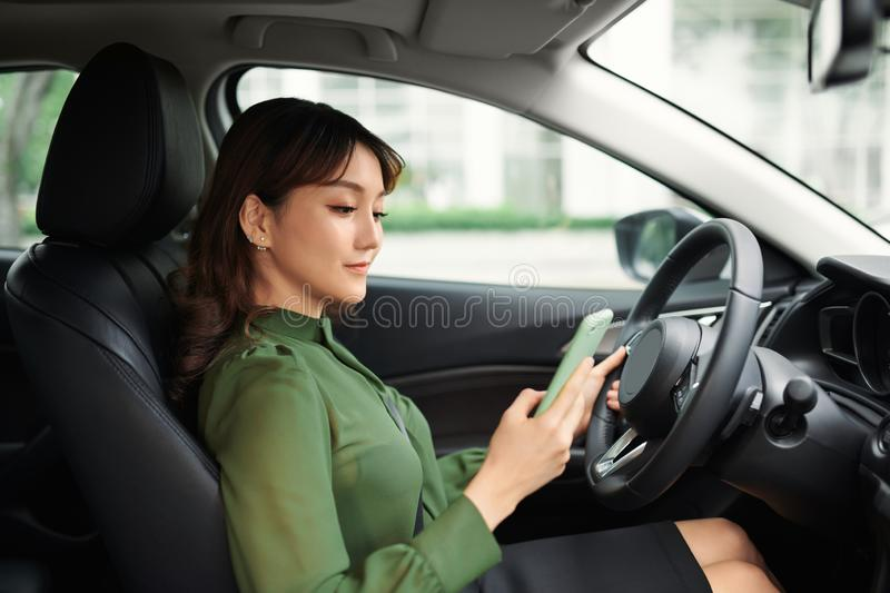 Young woman with mobile phone sitting in car royalty free stock photography