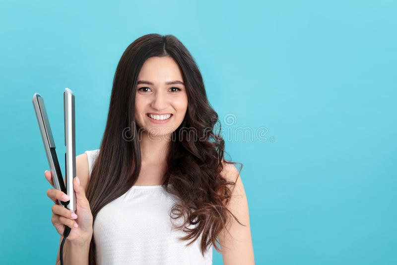 Young woman with modern hair iron on blue background royalty free stock images