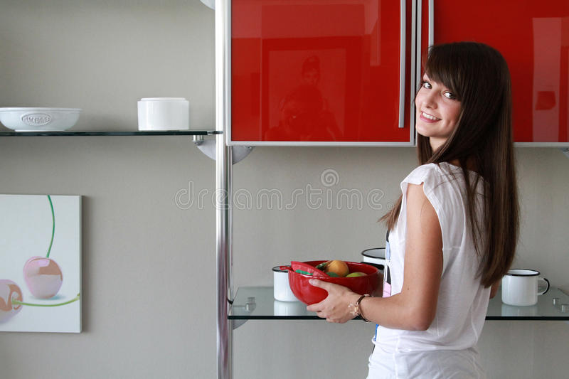 Young woman in modern kitchen. Holding red bowl of fruit, dimple, smiling royalty free stock image