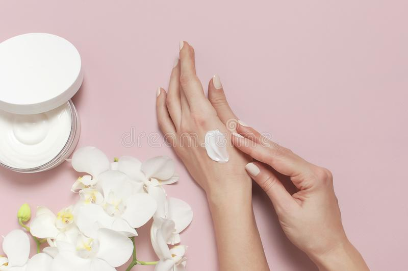 Young woman moisturizes her hand with cosmetic cream lotion opened container with cream body milk White Phalaenopsis orchid stock photo