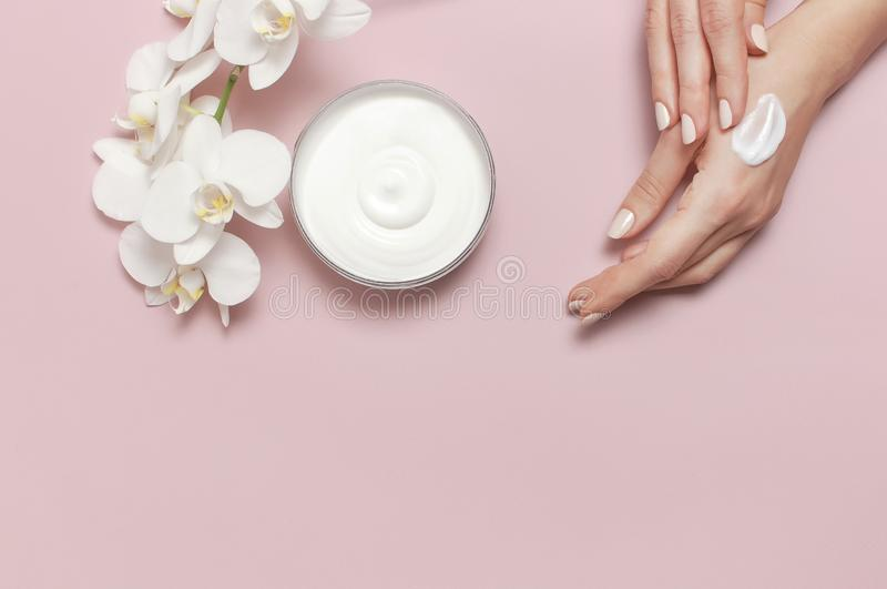 Young woman moisturizes her hand with cosmetic cream lotion opened container with cream body milk White Phalaenopsis orchid royalty free stock images