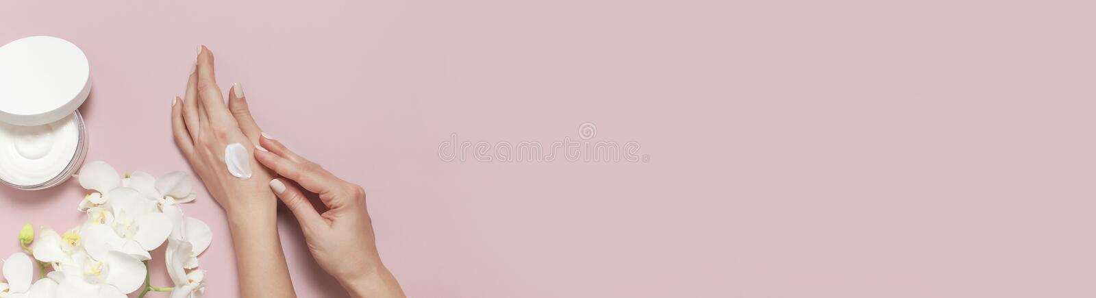 Young woman moisturizes her hand with cosmetic cream lotion opened container with cream body milk White Phalaenopsis orchid royalty free stock photos