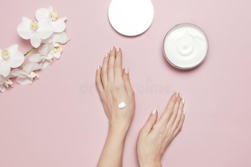 Young woman moisturizes her hand with cosmetic cream lotion opened container with cream body milk White Phalaenopsis stock photos