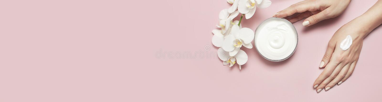 Young woman moisturizes her hand with cosmetic cream lotion opened container with cream body milk White Phalaenopsis royalty free stock photos
