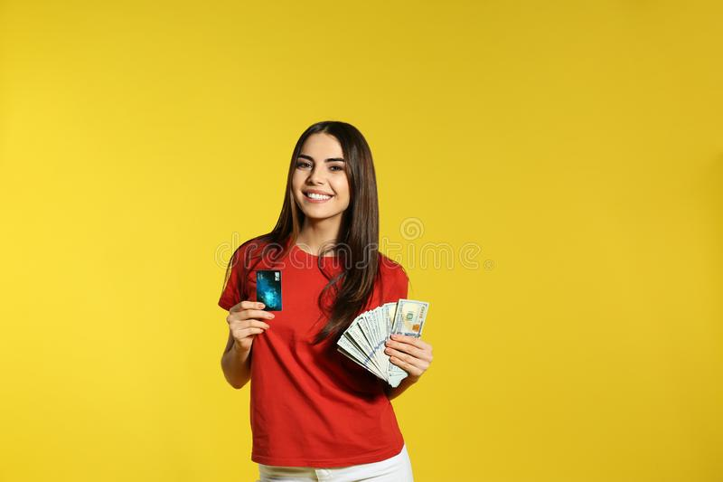 Young woman with money and credit card on color background. Space for text royalty free stock images