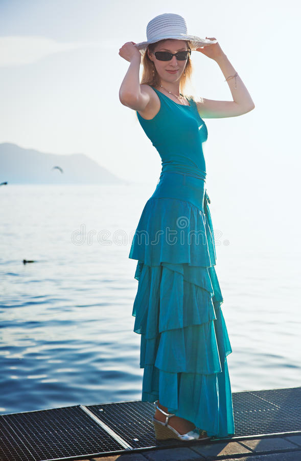 Young woman at the moorage. Young woman in blue dress standing at the moorage stock photography