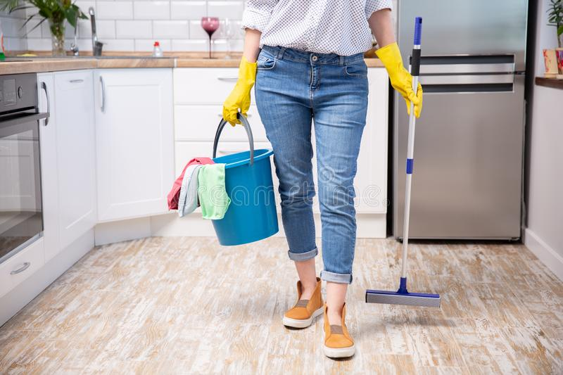 Young woman with mop and detergents in kitchen, closeup. Cleaning service royalty free stock photos