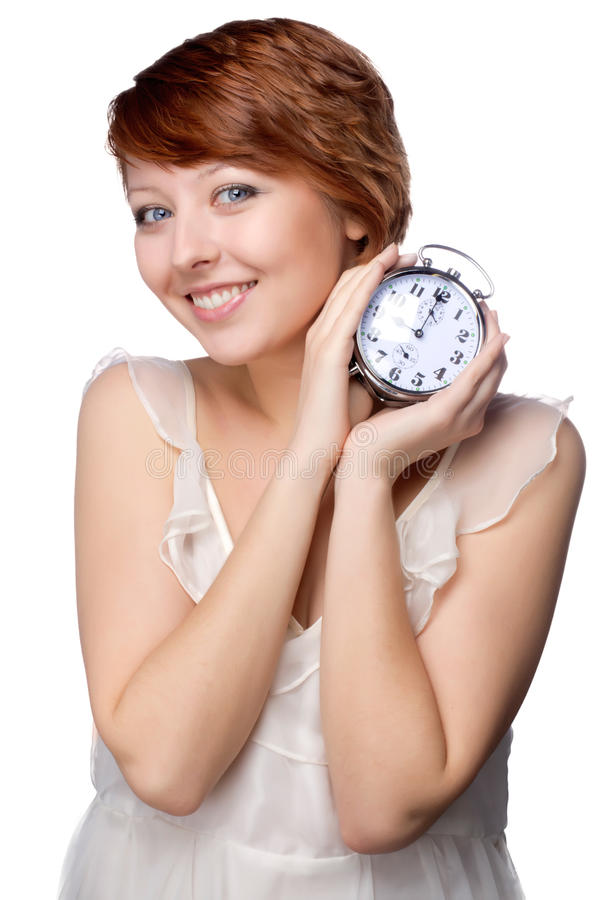 Young woman at morning with the clock. Young attractive woman with the clock over white background stock photo