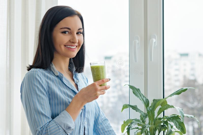 Young woman morning at home near the window drinking freshly blended green kiwi fruit smoothie in glass, vitamin drink in winter. Spring season, healthy food stock photo
