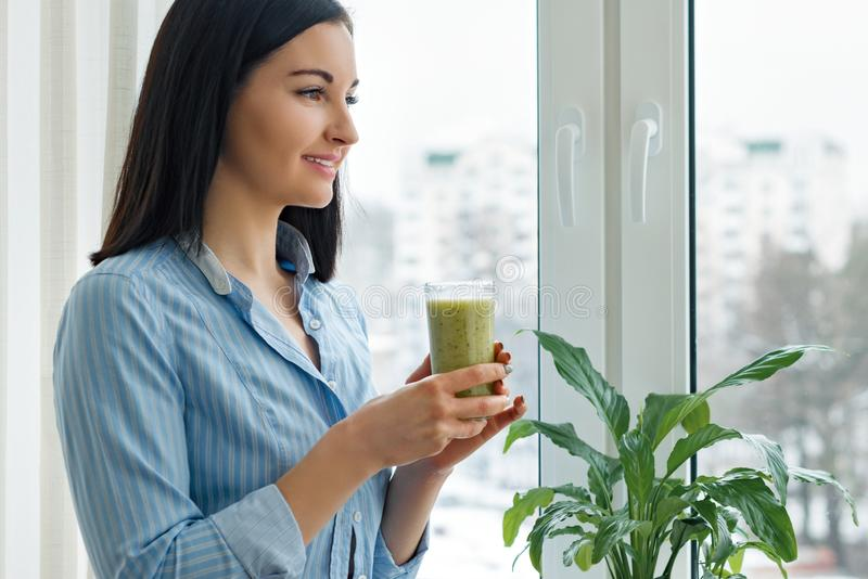 Young woman morning at home near the window drinking freshly blended green kiwi fruit smoothie in glass, vitamin drink in winter. Spring season, healthy food royalty free stock photo
