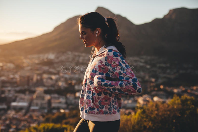 Young woman on morning walk. Side view of young caucasian woman on morning walk. Woman walking outdoors. Healthy lifestyle stock photography