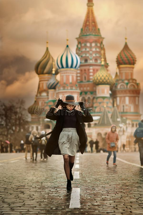 Young woman in Moscow Red Square. Young woman in vintage style walking near Sant Basil Cathedral in Moscow Red Square royalty free stock photo