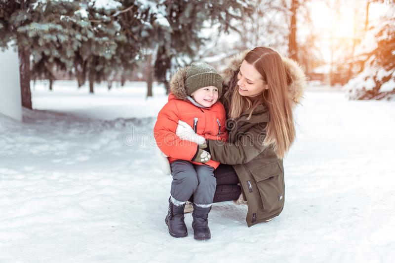 Young woman mother winter street, plays with her young son boy 3 years. Happy smiling, weighing up, laughing rejoicing royalty free stock image