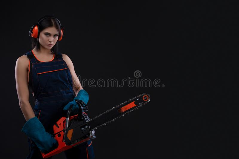 Young woman with motor saw or chainsaw on a black background royalty free stock image